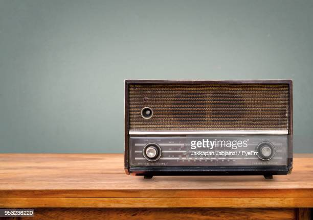 vintage radio on table against green wall - radio stock pictures, royalty-free photos & images
