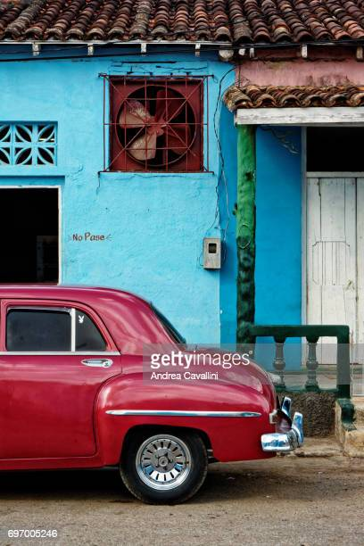 vintage red car  against a blue wall - cuba - cuba foto e immagini stock