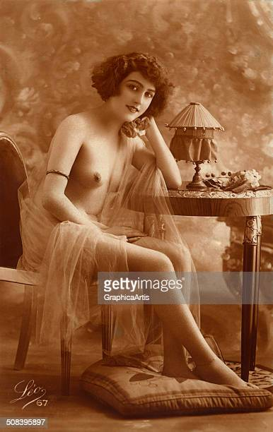 Vintage risque photograph of a seminude French woman in her boudoir c 1915 Toned silver print