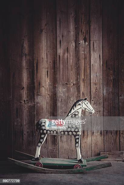 Vintage rocking horse in a barn in front of a wooden wall