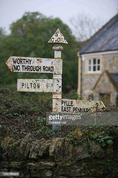 Vintage rural road signs in Somerset, England, with a traditional stone house in the background.