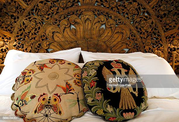 Vintage Russian pillows sit on the bed framed by a headboard converted from an intricate teakwood ceiling sculpture appoint the master bedroom of the...