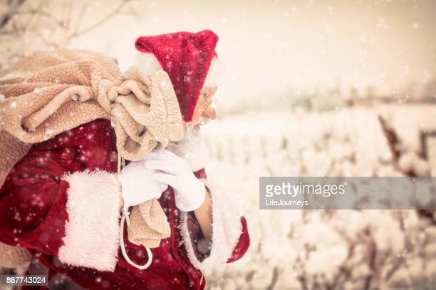 Vintage Santa Carrying His Pack Of Toys In A Winter Storm
