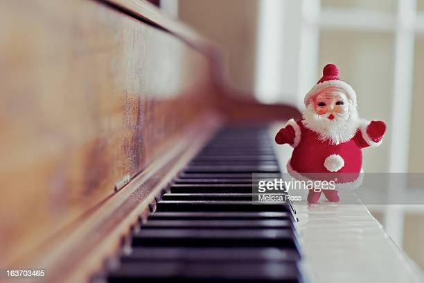 Vintage Santa Claus standing on piano keys