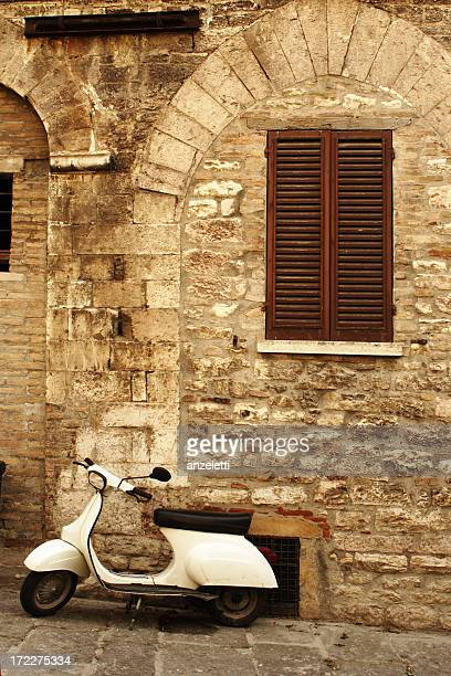 Vintage scene of a stone wall, wooden shudders and a moped
