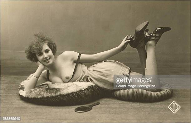 Vintage sepia toned black and white photograph of a female model with bared breasts wearing a short shift with heels and stockings lying on her side...