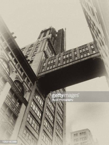 vintage, sepia-toned rendition of a new york city landmark: elevated passageway between two buildings in midtown manhattan - between stock pictures, royalty-free photos & images
