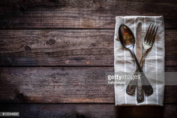 Cubiertos antiguos en textil servilleta tiro desde arriba en la mesa de madera rústica