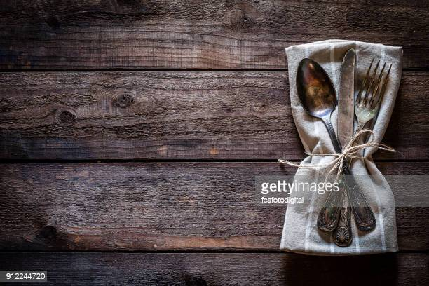 vintage silverware on textile napkin shot from above on rustic wooden table - eating utensil stock photos and pictures