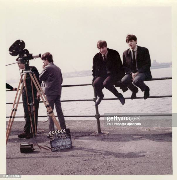 Vintage snapshot featuring John Lennon and Paul McCartney of the Beatles sitting on a railing beside the River Mersey in Liverpool during filming for...