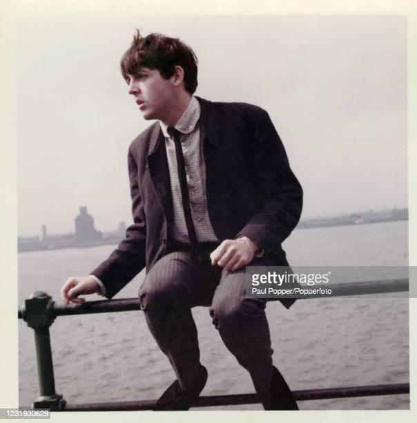 Vintage snapshot featuring Paul McCartney of the Beatles sitting on a railing beside the River Mersey during filming for the BBC TV documentary 'The...