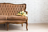 vintage sofa with flowers over white brick wall