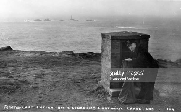 Vintage souvenir photo postcard depicts mailman servicing the last mailbox and Longships Lighthouse at Land's End in Cornwall England