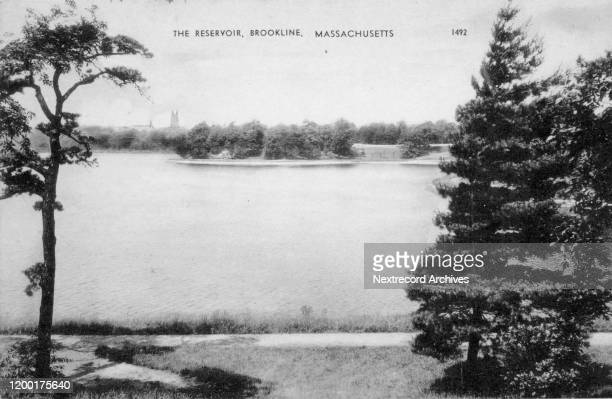 Vintage souvenir photo postcard published circa 1927 of the historic Reservoir in Brookline, Massachusetts, with the spire of the church at Boston...