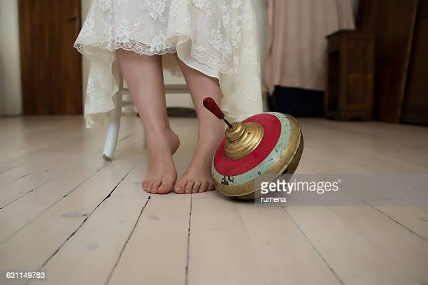 Vintage spinning top at girl's feet