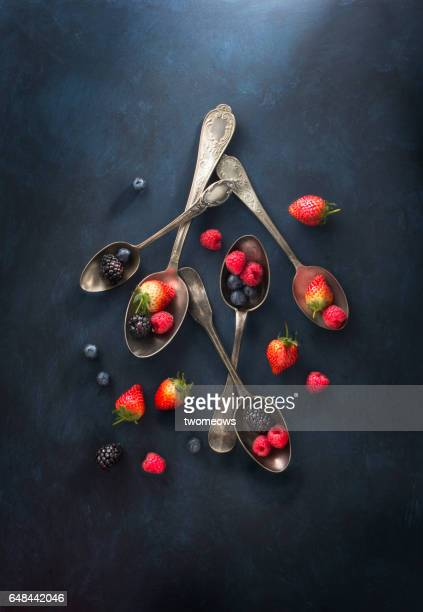 Vintage spoon and assorted berry fruits on textured dark blue background.