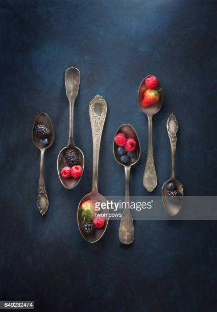 Vintage spoons and assorted berry fruits on textured dark blue background.