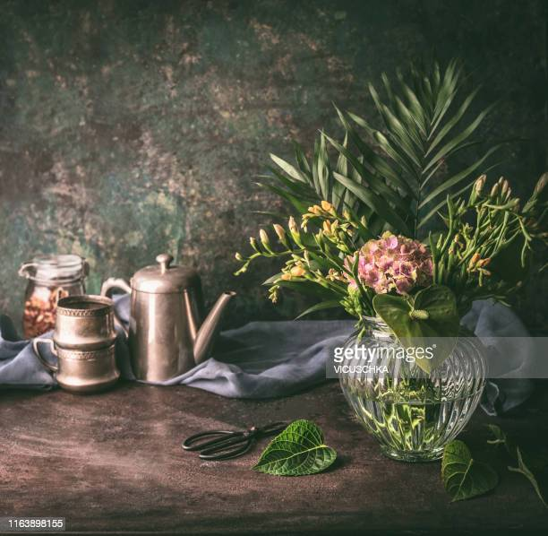 vintage still life with glass vase , flowers and tea set - still life foto e immagini stock