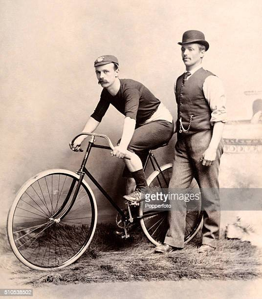 A vintage studio portrait featuring a competitive cyclist on his bicycle with his trainer alongside photographed in Blyth Northumberland circa 1910