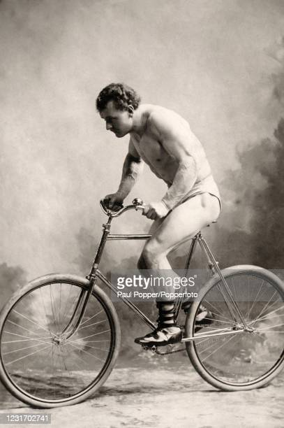 Vintage studio portrait featuring Eugene Sandow, German bodybuilder and showman, wearing briefs and sandals astride a bicycle, published in London,...
