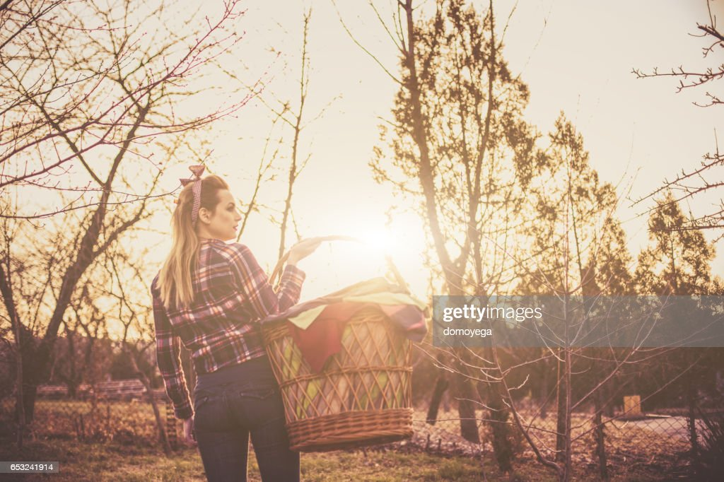 Vintage style girl carrying a laundry basket : Stock Photo