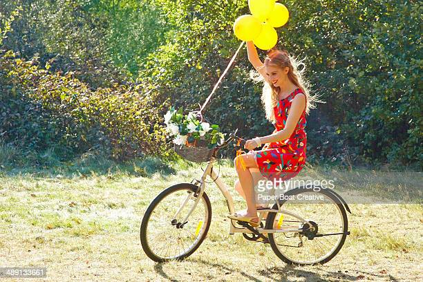 Vintage Style Photo of a woman biking with balloon