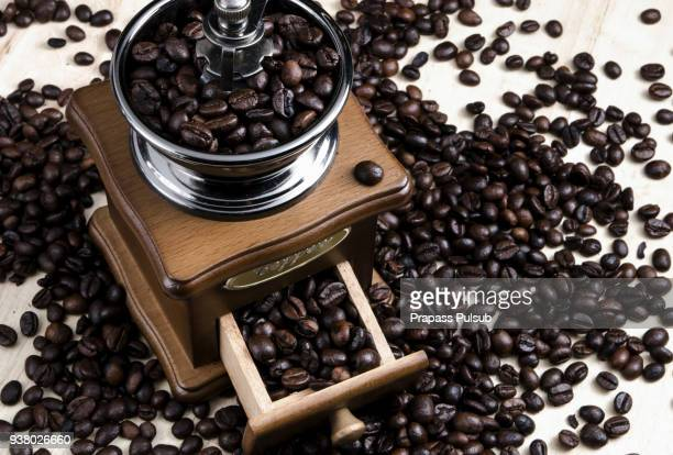 Vintage style photo of the roasted coffee beans in a coffee grinder with blur cinnamon and coffee beans background