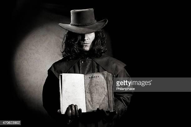 vintage style wild west gunslinger holding ancient bible book