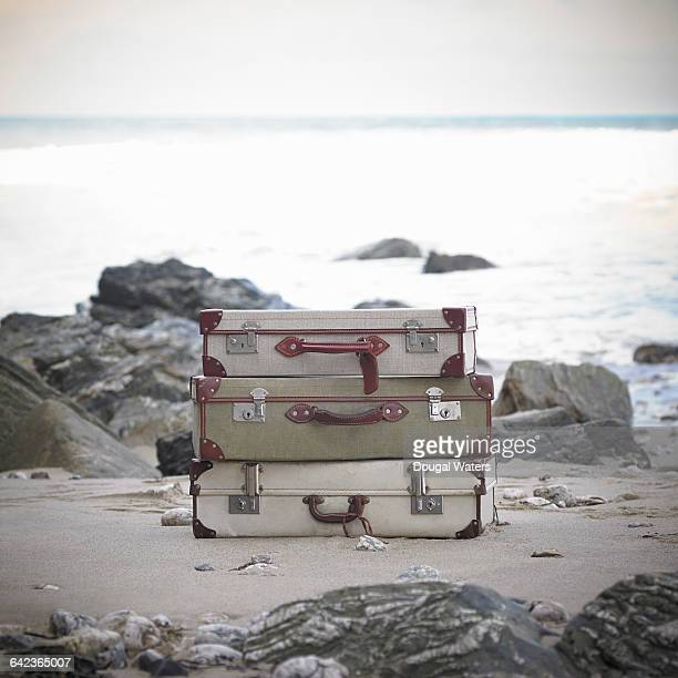 vintage suitcases on rocky beach. - dougal waters stock pictures, royalty-free photos & images