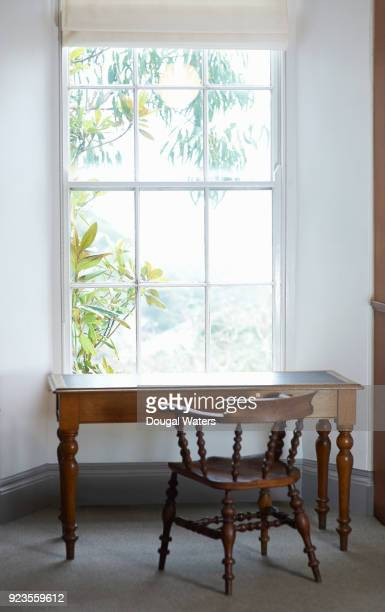 Vintage table and chair beside library window.