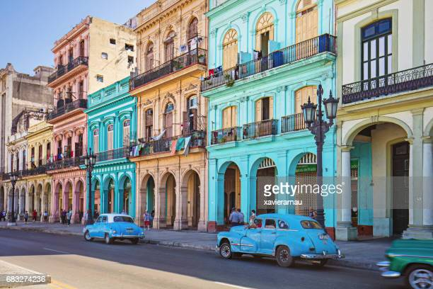 vintage taxis on street against historic buildings - cuba foto e immagini stock