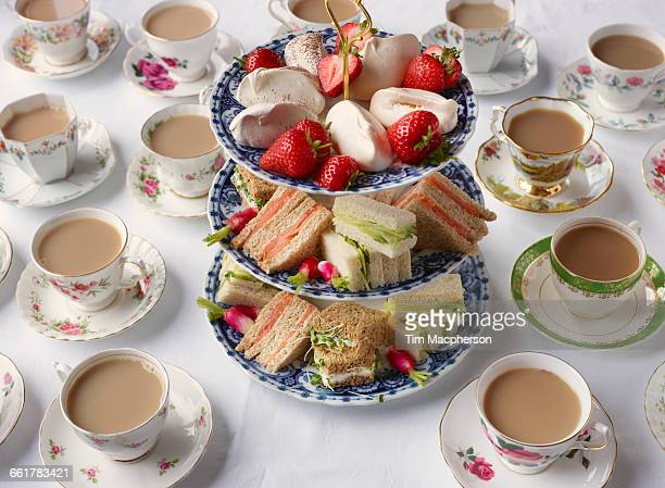 vintage tea cups and sandwiches on cakestand prepared for afternoon tea - afternoon tea stock pictures, royalty-free photos & images