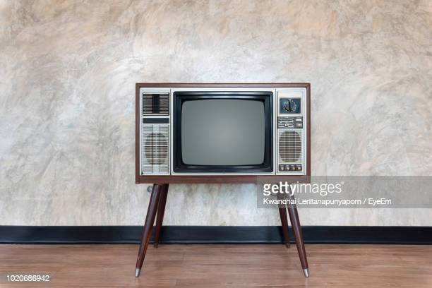 vintage television set on floor against wall - televisietoestel stockfoto's en -beelden