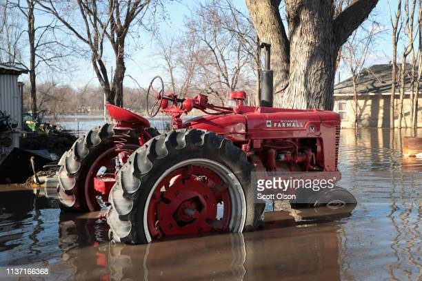A vintage tractor sits in flood water on March 20 2019 in Hamburg Iowa Although flood water in the town has started to recede many homes and...