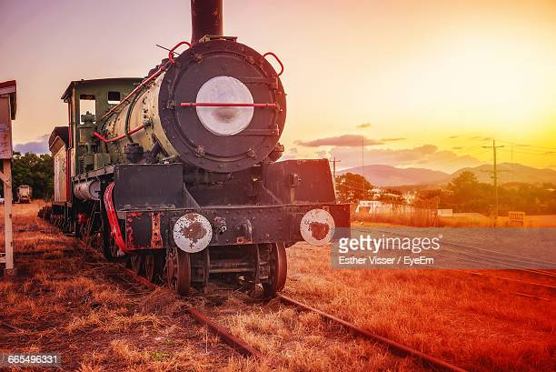 Vintage Train On Field Against Sky During Sunset