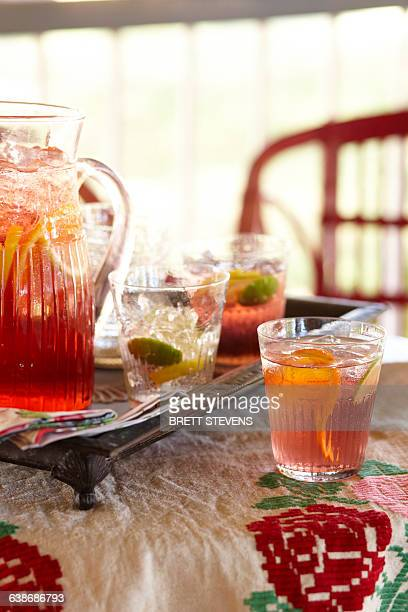 Vintage tray with jug and glasses of cinzano punch and lime slices