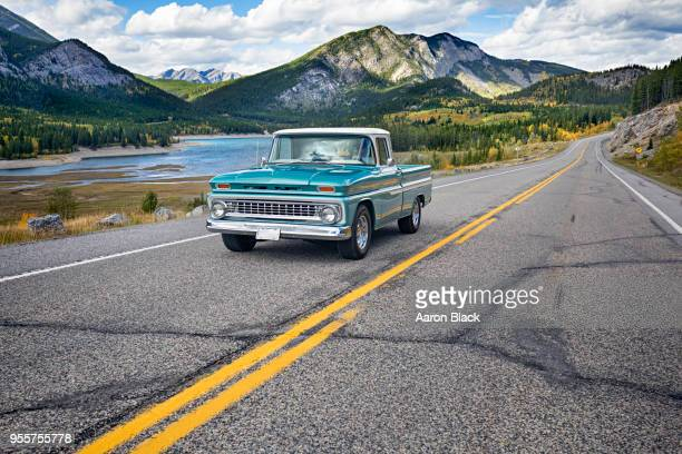 vintage turquoise pick up driving on a highway past a lake, forest and mounatins. - kananaskis stock-fotos und bilder