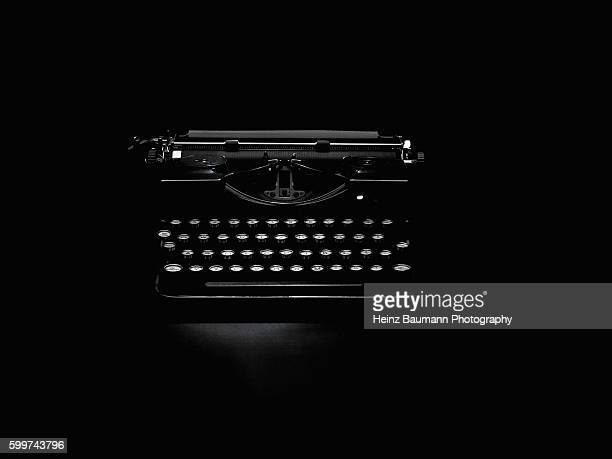 vintage typewriter on black background - heinz baumann photography stock-fotos und bilder