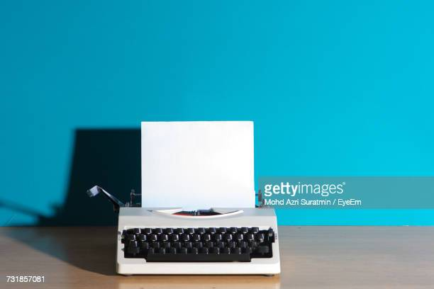 Vintage Typewriter On Desk Against Blue Wall