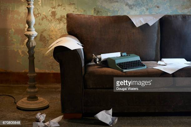 Vintage typewriter on sofa with lamp and paper on floor.