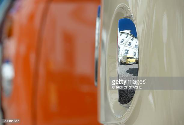 A vintage Volkswagen bus reflects in the head lamp of another one standing in front of the abbey Schaeftlarn near Munich southern Germany during an...