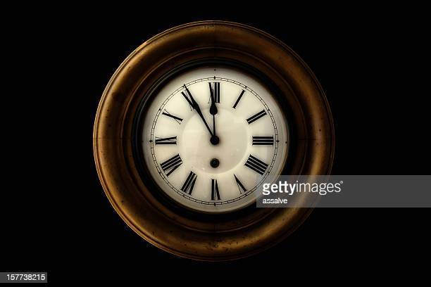 vintage wall clock showing five minutes to midnight
