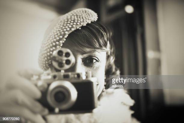 Vintage woman at bar counter making photos with old camera and looking directly into the camera