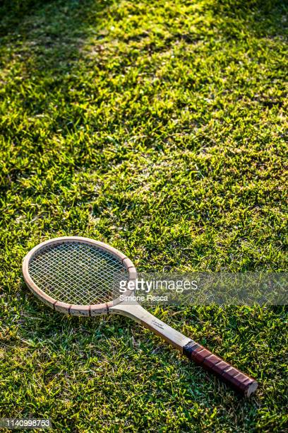 vintage wood tennis racket on grass garden - tennis racquet stock pictures, royalty-free photos & images