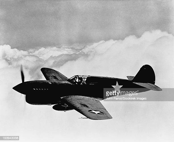 Vintage World War II photo of a P-40 fighter plane flying above the clouds.