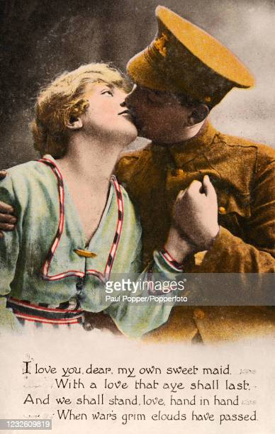 Vintage World War One Valentine postcard featuring a British soldier in uniform kissing his sweetheart above a love poem, published in England, circa...