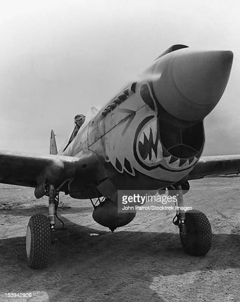 Vintage World War Two image of a P-40 Warhawk plane with a Flying Tigers paint scheme.