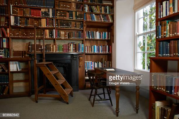Vintage writing desk, chair and steps in traditional library.
