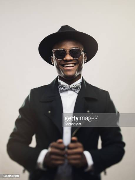 vintage young man wearing black suit and hat - nigerian men stock photos and pictures