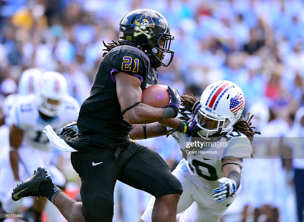 Vintavious Cooper #21 of the East Carolina Pirates runs against Tre Boston #10 of the North Carolina Tar Heels during play at Kenan Stadium on September 28, 2013 in Chapel Hill, North Carolina. East Carolina won 55-31.